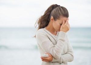 http://www.dreamstime.com/stock-image-stressed-young-woman-sweater-beach-cell-phone-long-hair-image34522101